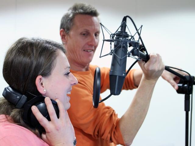 Layouter Andi Baumann richtet Angela das Mikrofon.