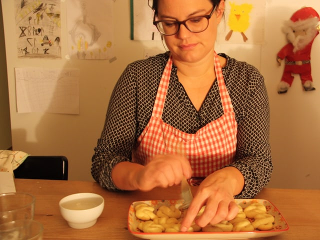 Eine Frau mit Küchenschürze sitzt an einem Tisch und glasiert Kekse.
