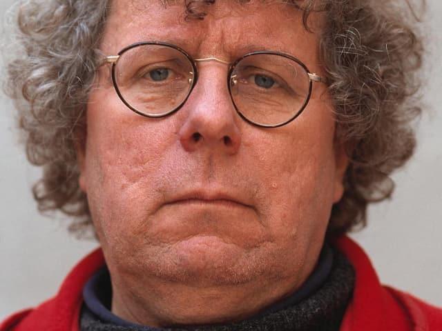 Loderer trägt eine Brille mit einem leichten Gestellt, seine grauen Locken fallen ihm in die Stirn.