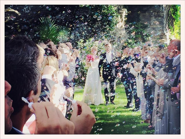 Das Brautpaar umringt von Gästen und Seifenblasen