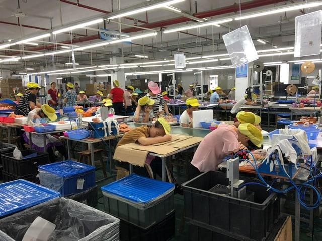 Fabrikarbeiter schlafen am Arbeitsplatz.