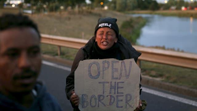 Ina migranta tegn in chartun cun l'inscripziun d'avrir il cunfin.