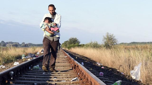 Syrischer Flüchtling mit Kind an der ungarischen Grenze zu Serbien.