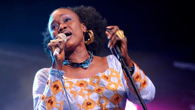 Schwarze Frau im weissen Kleid: die Sängerin Oumou Sangaré bei einem Konzert.