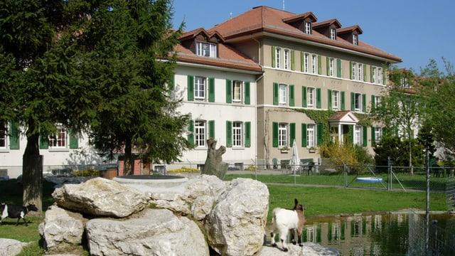 Das Hauptgebäude des Altersheims Kühlewil mit Teich und Ziegen davor.