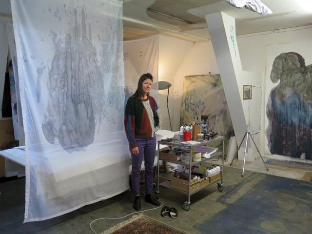Zierliche Frau steht mitten im Raum, um sie herum hangen bemalte Leintüchern von der Decke