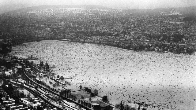Auf dem zugefrorenen Zürichsee tummeln sich viele Menschen.