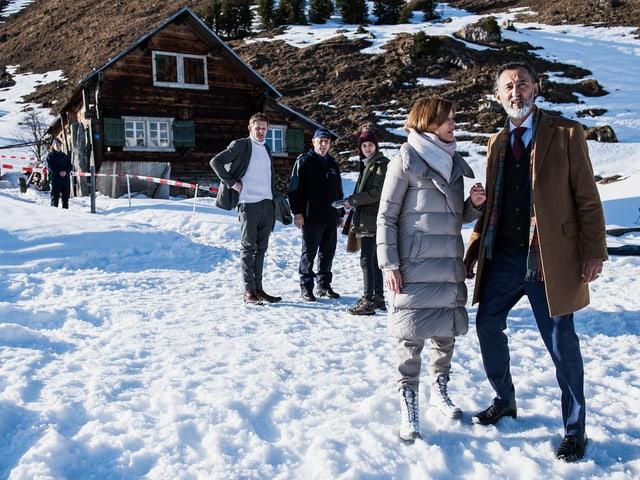 Eine Gruppe von Menschen steht mit ernsetn gesichtern in einer verschneiten Landschaft.