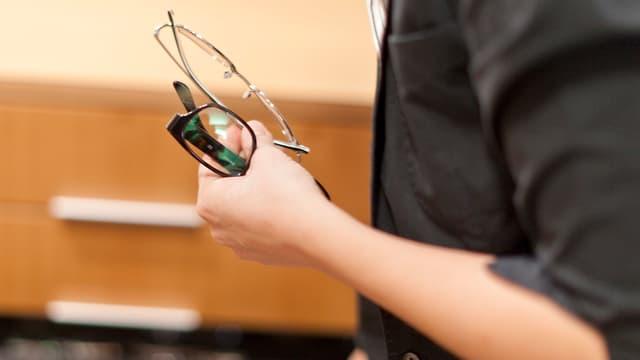 Eine Frau hält zwei Brillenmodelle in der Hand.