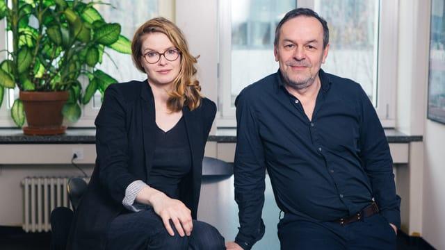 Eine Frau und ein Mann sitzen nebeneinander und schauen in die Kamera.