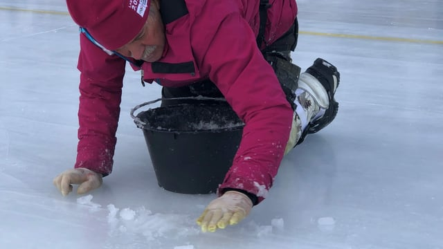Mit Schneematsch bessert Louis Schönbächler Risse im Eis aus.