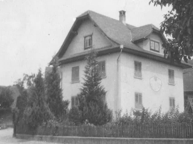 Schwarz-Weiss Fotografie mit einem dreistöckigen Haus an einer Strassenecke.