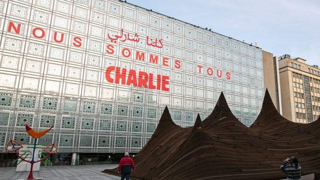 """Auf einer Fassade steht in grossen roten Buchstaben """"Nous sommes tous Charlie"""", neben arabischen Schriftzeichen."""