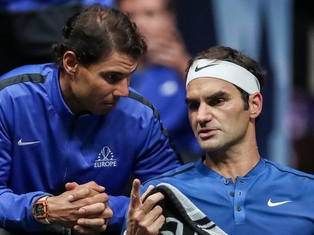 Roger Federer auf der Spielerbank unterhält sich mit Rafael Nadal.
