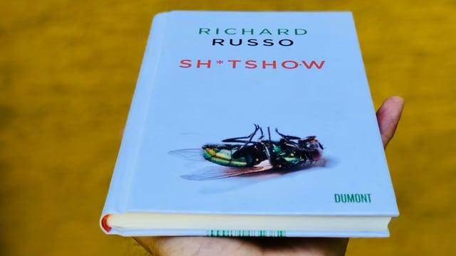 Das Buch «Sh*tshow» von Richard Russo vor einem ockerfarbenen Hintergrund