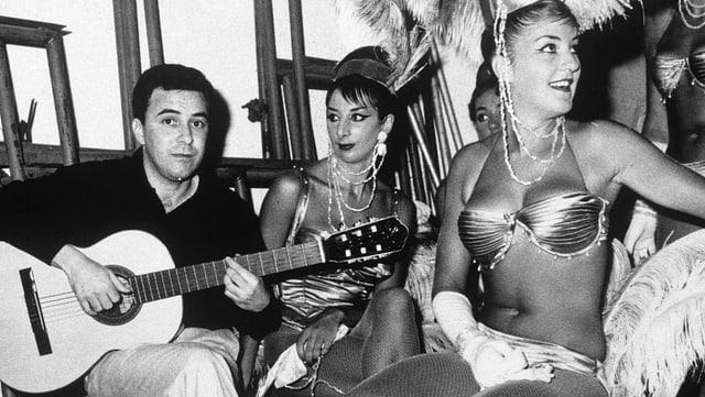 Gitarrist Joao Gilberto sitzt neben zwei Tänzerinnen, die mit Federn geschmückt sind.