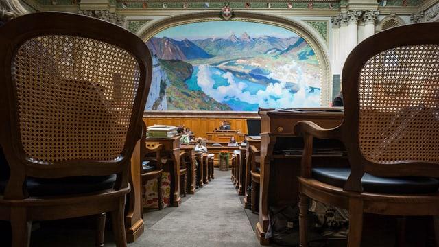 Ein Bild mit See und Wolken im Nationalratssaal, davor leere Stühle.