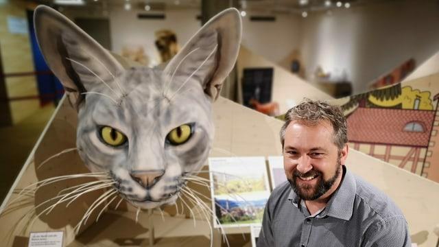 Mann neben grossem Katzenkopf