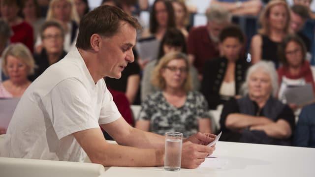 Ein Mann in weissem Shirt liest an einem tisch von einem Blatt.