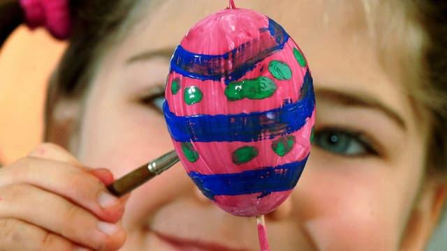 Ein Kind mal ein Ei an.