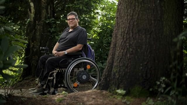 Ein Mann im Rollstuhl umringt von Bäumen