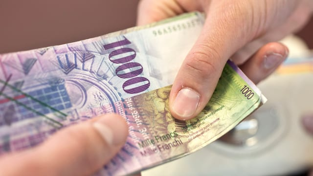 Eine Person gibt an eine andere mehrere tausend Franken.