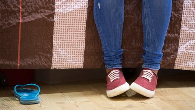 Beine eines Mädchens, das auf einem Bett sitzt