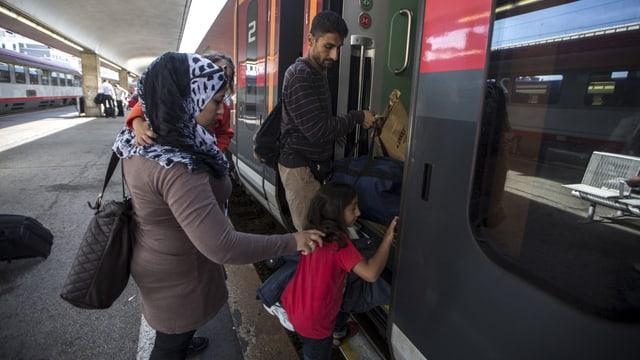 Eine Frau und ein Mann mit zwei Kindern besteigen einen Zug in Wien