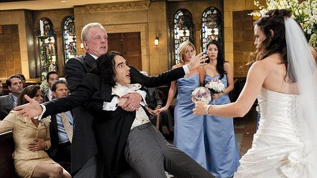 Ein Mann fliegt einem anderen Mann in der Kirche in die Arme, davor steht seine Braut.