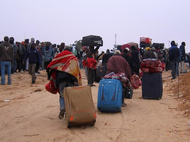 Flüchtlinge ziehen ihre Rollkoffer durch den Sand