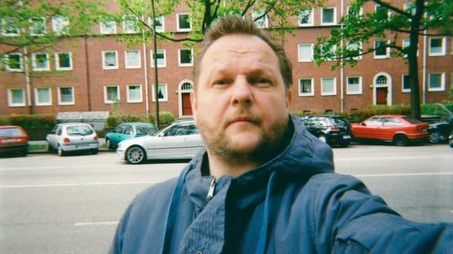 Mann auf der Strasse – im Hintergrund eine Häuserzeile.