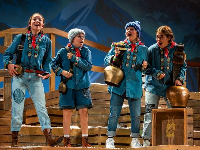 Vier Kinder in traditioneller Schweizer Kleidung stehen auf Holzkisten und singen. Alle tragen eine Glocke um den Arm. Sie spielen Kinder aus dem Kinderbuchklassiker Schellen-Ursli