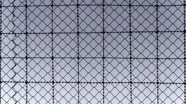 Ein Gitterzaun eines Gefängnisses.