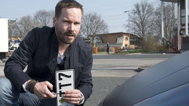 Wanja Mues als Privatdetektiv Leo Oswald kniet vor einem Auto mit dem Nummernschild in der Hand.