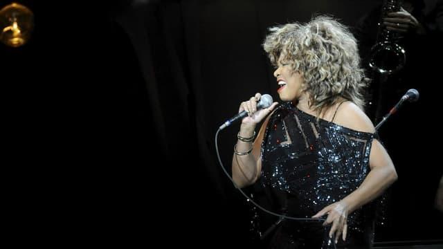 Purtret da Tina Turner durant in concert.