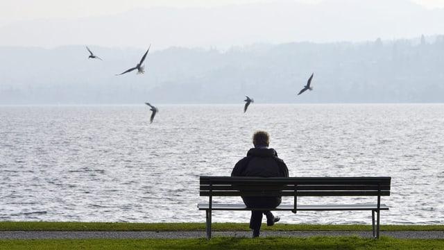 Ein Mann sitzt allein auf einer Bank am See.