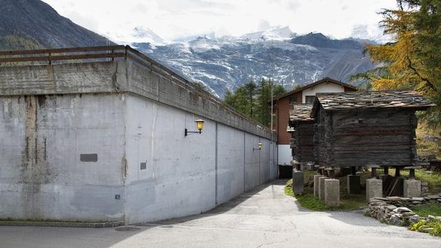 Zu sehen ist eine Betonwand und alte Holzscheunen.