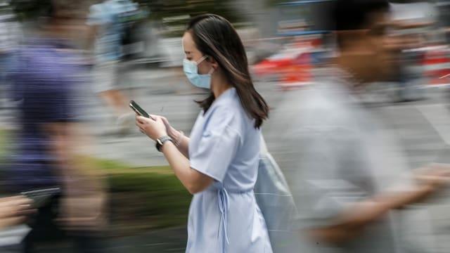 Eine Frau rennt mit einer Maske rum.