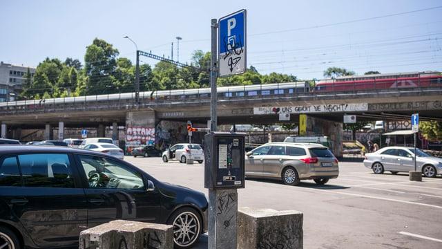 Autos, Eisenbahnbrücke, Parkuhr auf der Berner Schützenmatte.