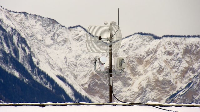 Antenne auf Hausdach, im Hintergrund ist ein Berg erkennbar