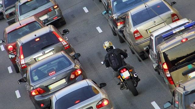 Autokolonnen und ein Motorradfahrer auf einer Autobahn.