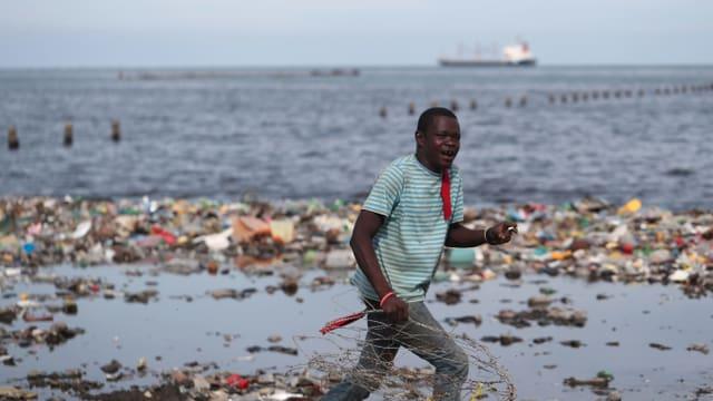 Mann vor Plastik-Müllbergen.