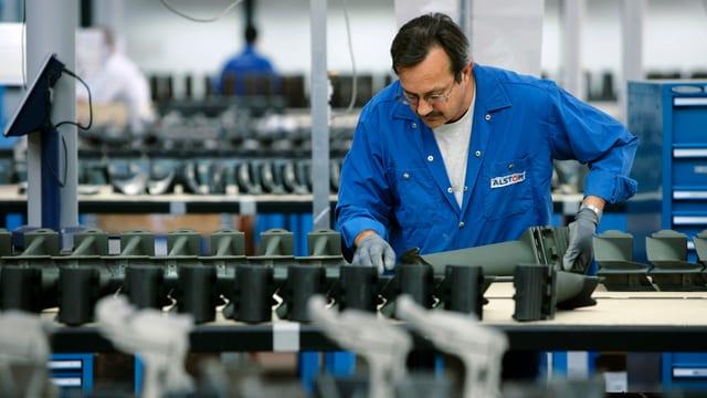 Ein Arbeiter von Alstom mit blauem Arbeitskittel an einem Laufband in der Fabrik in Birr.