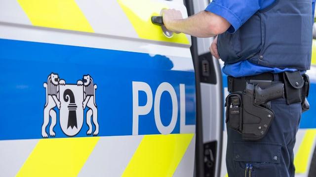 Ein Polizist, dessen Gesicht nicht zu sehen ist, öffnet ein Polizeiauto