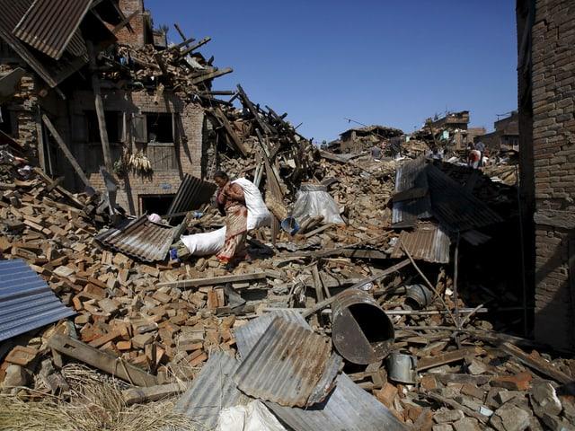 Eine Frau geht über die Trümmer.