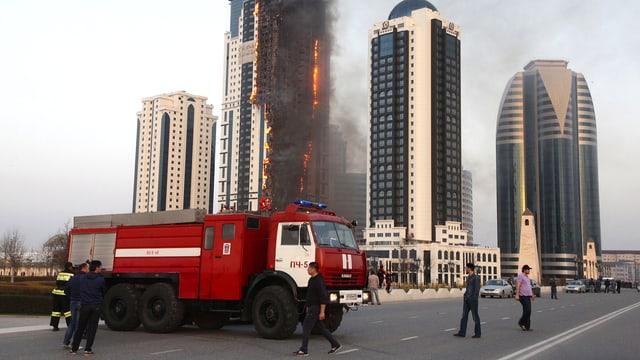 Ein Hochhaus steht in Flammen. Im Bildvordergrund ist ein rotes Feuerwehrauto zu sehen.