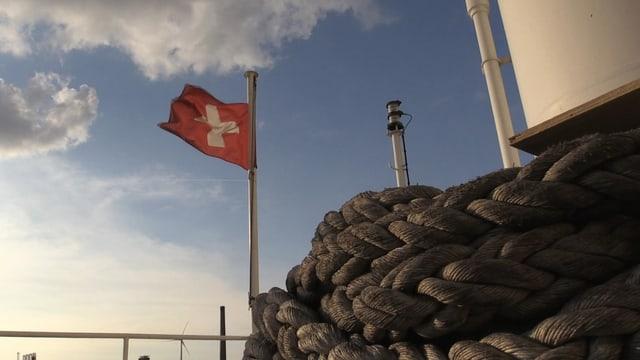 Schweizer Flagge und Taue auf Frachtschiff.