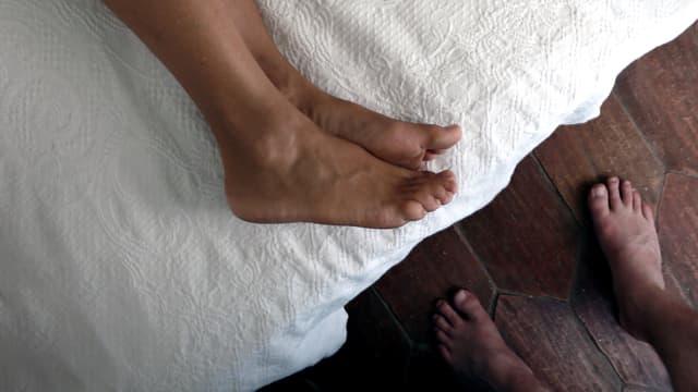 Ein paar Füsse steht vor einem Bett. Auf dem Bett liegen zwei Beine.