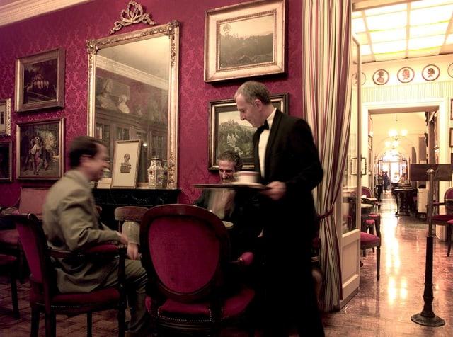 Ein Kellner und zwei Gäste Im Inneren des Caffè Greco.