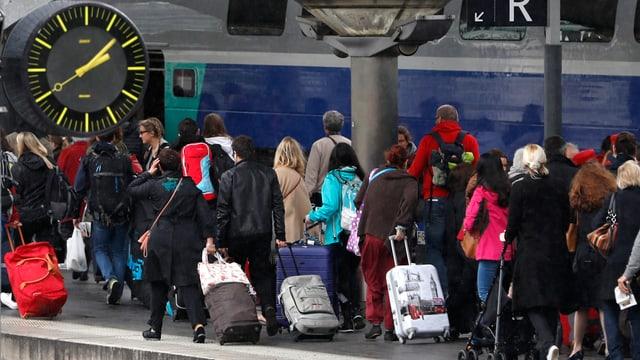 Personen mit Rollkoffern auf einem Bahnsteig.